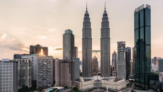 tl/zo zoom out time lapse/hyper lapse of the petronas towers and kuala lumpur skyline at sunset - petronas twin towers stock-videos und b-roll-filmmaterial