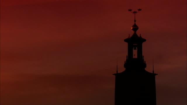PAN to WS Almost silhouette of top of Stockholm City Hall monumental tower w/ Three Crowns on Kungsholmen island Scandinavia