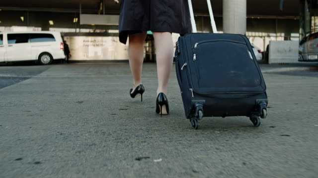 cu to ms businesswoman walking with suitcase outside airport - suitcase stock videos & royalty-free footage