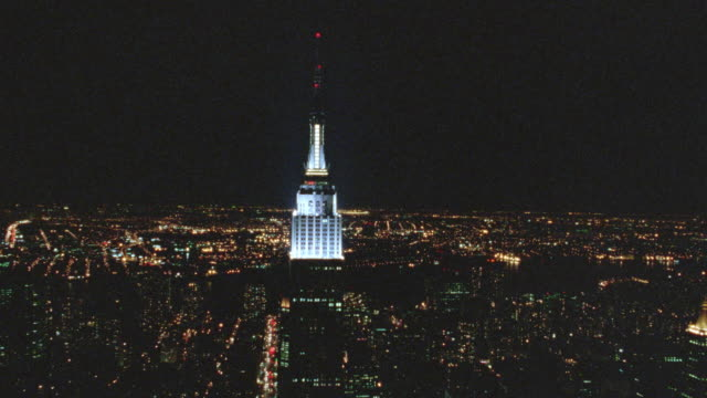 vídeos de stock, filmes e b-roll de aerial to close up of empire state building at night / nyc - 2001