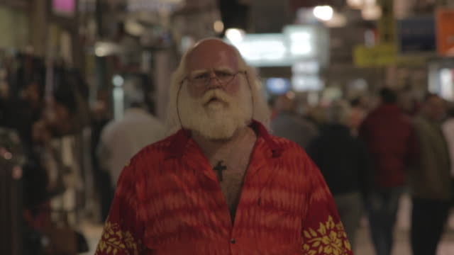vídeos y material grabado en eventos de stock de m/s to c/u big man w/ white long hair (santa claus), beard and moustache, hawaiian shirt, walking in a commercial street by night - moustache
