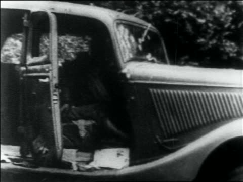 vidéos et rushes de pan to dead bodies of bonnie and clyde in car / louisiana - 1934
