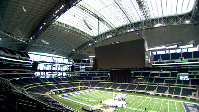 to empty cowboys stadium arena, unidentifiable people setting up stage in middle of football field. tx, concert, rehearsal, fight, show, presentation - large scale screen stock videos & royalty-free footage