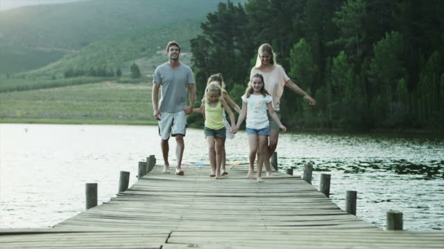 ws to ms of family walking along jetty by lake - family with three children stock videos & royalty-free footage
