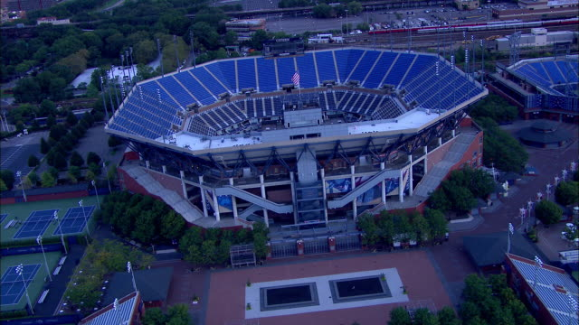 vídeos de stock, filmes e b-roll de tu to ws flyover empty tennis courts empty arthur ashe stadium in flushing meadows park partial louis armstrong stadium bg nyc - flushing meadows corona park