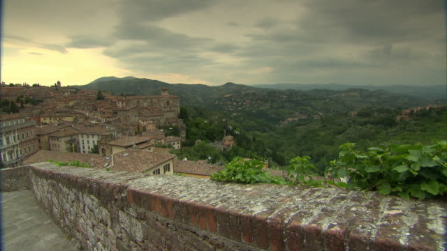 to perugia city in valley of residential homes, houses, trees around, hills & mountains stretching into distance, setting sun bg. - perugia stock videos & royalty-free footage