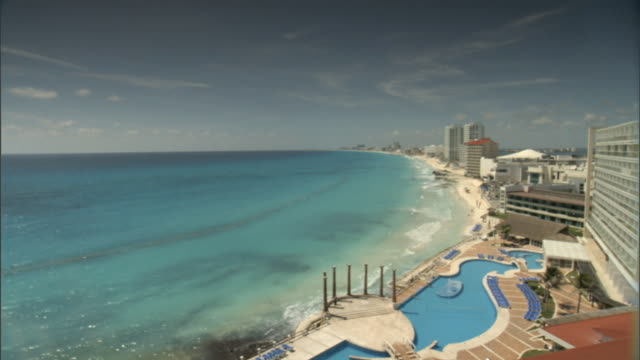 to ha ws from yucatan channel water to highrise buildings along the coastline stretching into distant bg resort pool lower frame mx - cancun stock videos & royalty-free footage
