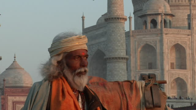 ZO CU to MS gray-haired man (Sadhu) standing with camel in Yamuna River with Taj Mahal in background / Agra, Uttar Pradesh, India