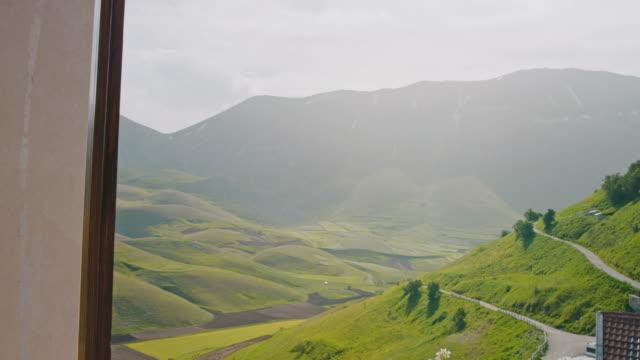 vídeos de stock e filmes b-roll de cu to ws hand parting curtains, revealing sunny idyllic mountain view, castelluccio, umbria, italy - janela aberta