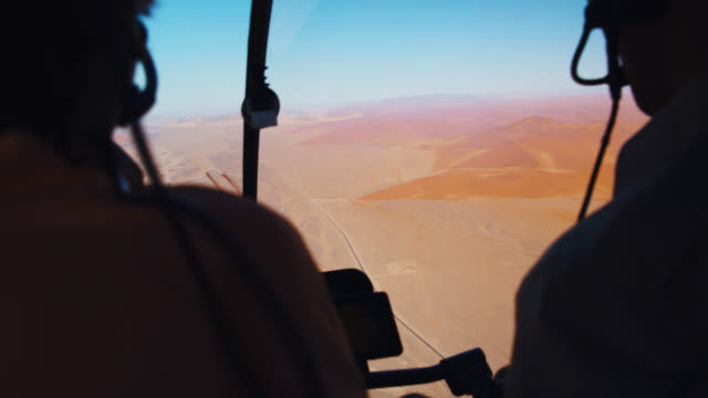cu to ms helicopter pilot and passenger flying over deadvlei dessert,namibia,africa - helicopter stock videos & royalty-free footage