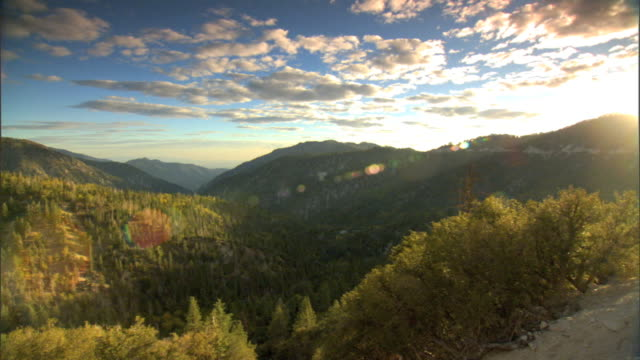 PAN to WS Hills w/ pine trees mountains stretching into distance partially cloudy sky top frame BG CA