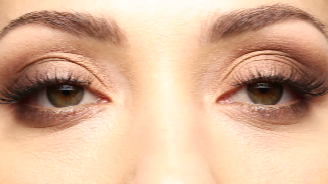 pan r to l in cu of young woman's brown eyes - brown eyes stock videos & royalty-free footage