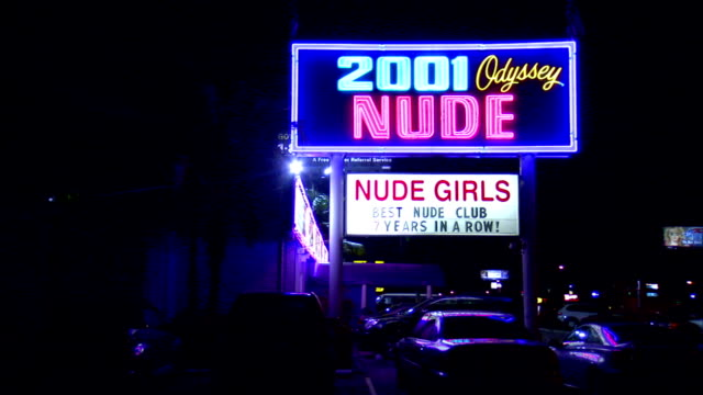 to LA WS Lit neon sign 2001 Odyssey Nude Nude Girls Best Nude Club 7 Years in a Row along North Dale Mabry Highway parked cars in lot lower frame...