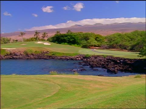 vídeos de stock, filmes e b-roll de pan to male golfer teeing off over water with mountains in background / mauna kea beach golf course, hawaii - obstáculo de água