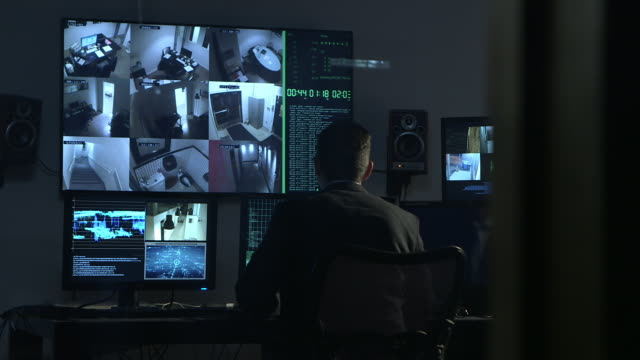 PAN to man looking at monitors of security surveillance system