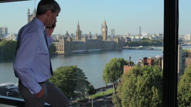 vídeos de stock e filmes b-roll de ms pan to man using phone with westminster in distance - camisa e gravata