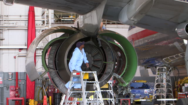 zi to mechanic working on jet  engine on plane in hanger/dfw international airport, dallas-fort worth, texas, usa - motore d'aeroplano video stock e b–roll