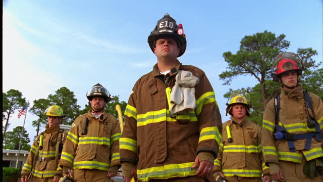 LOW ANGLE WIDE to MEDIUM DOLLY SHOT to group of firefighters in gear standing in front of fire station\n