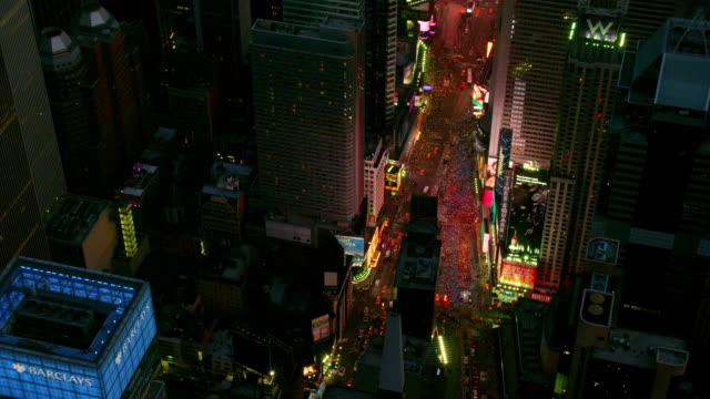 MEDIUM to OVERHEAD POV AERIAL over streets and buildings of Times Square at night