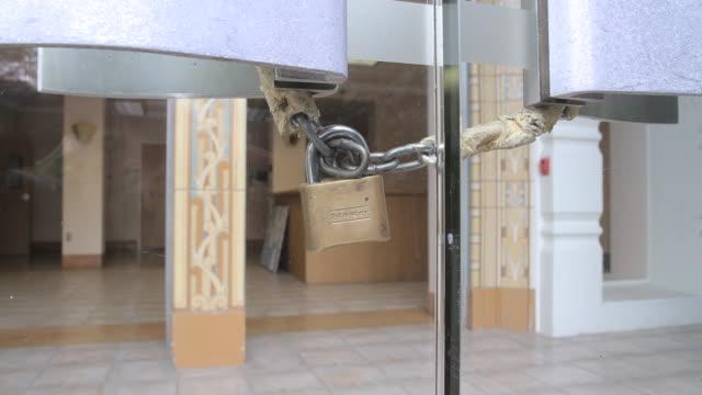 vídeos de stock, filmes e b-roll de zi to padlock on front doors of closed hospital - falência