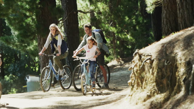 ws to ms pan r to l of family cycling along dirt road in forest, dirty frame shallow depth of field - two parents stock videos & royalty-free footage