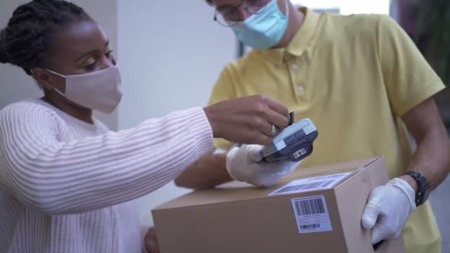 vídeos de stock, filmes e b-roll de para evitar que o vírus se espalhe pela mulher usando um pagamento sem contato para sua entrega de alimentos - receber