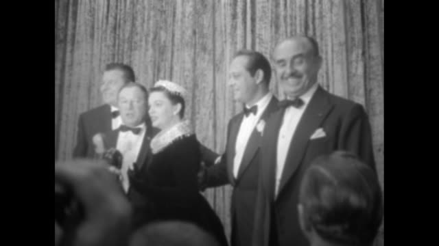 Jack Carson George Jessel Judy Garland Sidney Luft and Jack L Warner stand on stage at the Pantages Theatre prior to the movie premiere of A Star is...