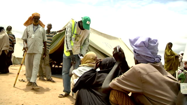 to refugees waiting in line Refugee camp officer giving a pass on July 31 2011 in Dadaab Kenya