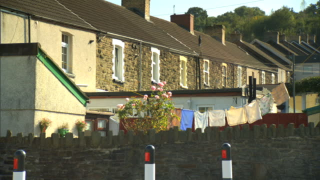 vídeos de stock e filmes b-roll de to row of houses on hill stretching into distance on town street, towels hanging on clothesline in yard, stone wall on street lower frame. uk - toalha