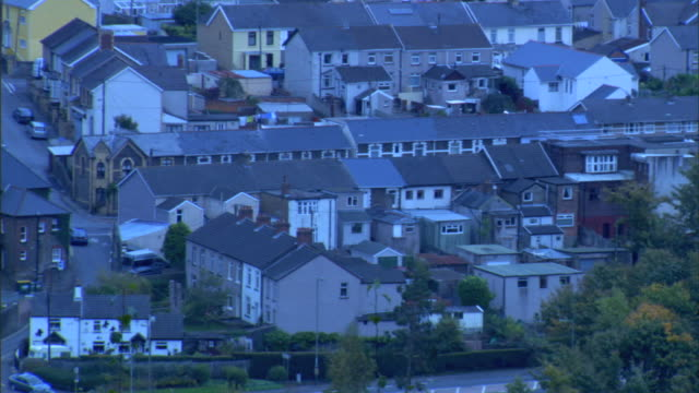 pan to ha ws rows rows of similarly designed connected residential houses some cars driving on streets below uk - terraced house stock videos & royalty-free footage