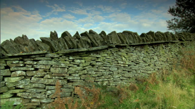 pan to ms slanted uneven stone rock wall on grass hill partially cloudy sky bg some grass lower fg uk - uneven stock videos & royalty-free footage