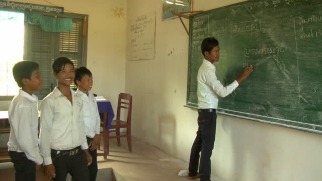 PAN to student writing on chalkboard  / Siem Reap, Cambodia