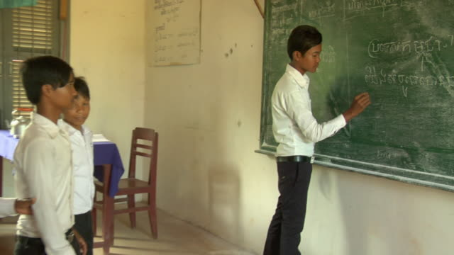 pan to student writing on chalkboard  / siem reap, cambodia - schoolboy stock videos and b-roll footage