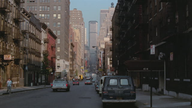 1969 ws pan zi tu to tall building facing a busy west 44th st./ midtown manhattan, new york, usa - 1969年点の映像素材/bロール