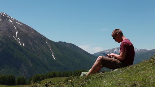 pan to teenage hiker using digital tablet in mtn meadow - männlicher teenager allein stock-videos und b-roll-filmmaterial