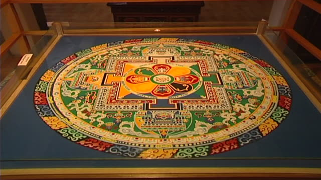 vidéos et rushes de to the center of an ornate red, green, yellow, and blue mandala, showing its intricate carving and symmetry. - littérature