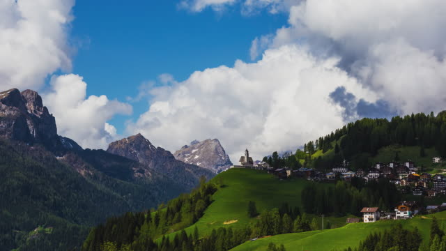 T/L ZOOM IN to the church right in front of the massive mountain range in the Italian Dolomites
