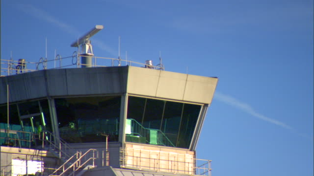 tu pan to ms top of air traffic control tower w/ rotating radar on roof out/in focus tower united kingdom uk - air traffic control点の映像素材/bロール