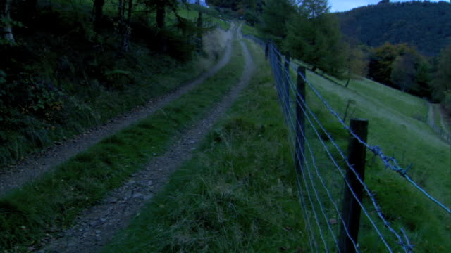 to unpaved countryside road, gravel trail tire tracks frame, barbed wired fence along roadside , trees, hills, grass, & mountain bg . uk, rural - mensch und maschine stock-videos und b-roll-filmmaterial