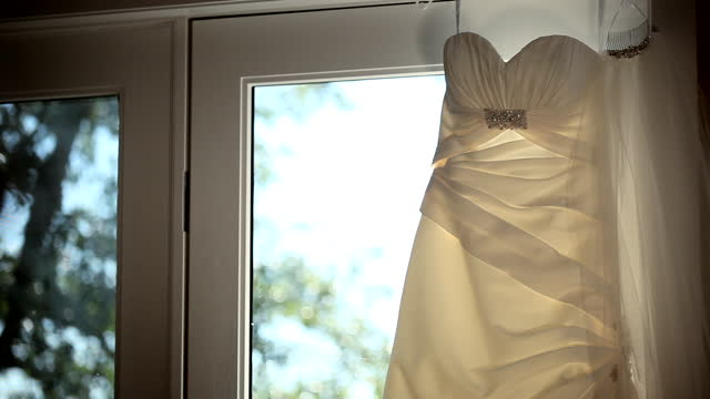 MEDIUM DOLLY SHOT to wedding dress and veil hanging in front of window