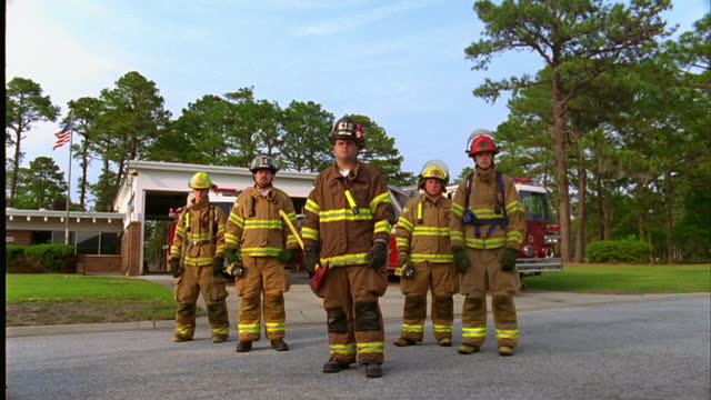 low angle medium to wide dolly shot away from group of firefighters in gear standing in front of fire station\n - heroes stock videos & royalty-free footage