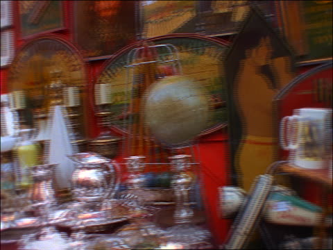 pan to woman in portobello road market in london displaying china - mercato delle pulci video stock e b–roll