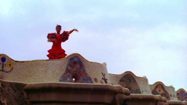 pan to woman in red flamenco dress dancing on roof / parc guell, barcelona, spain - flamenco dancing stock videos and b-roll footage