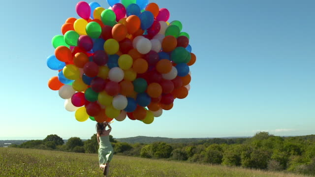 CU to WS woman running through field with large bunch of balloons