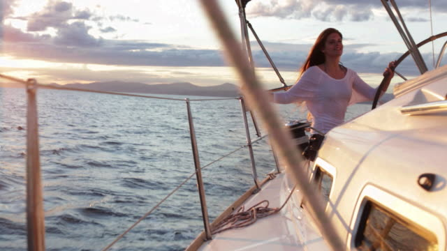 WS PAN to woman sitting on back of yacht steering.