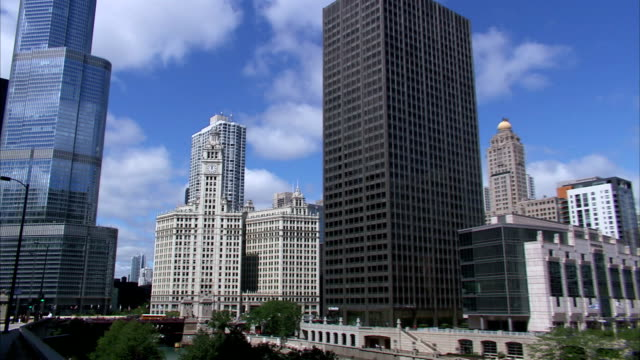 vídeos de stock, filmes e b-roll de to xws wrigley building in middle of urban chicago skyline , overlooking chicago river. il - chicago 'l'
