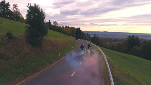 ms, ws jm reiten skateboards mit rauchbomben auf kurvenreichen landstraße - winding road stock-videos und b-roll-filmmaterial