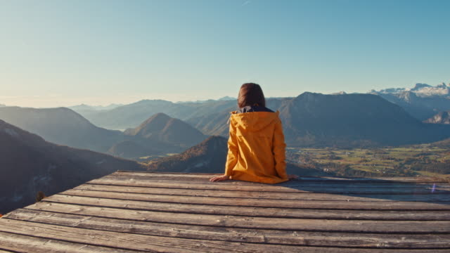 cu to ms young woman sitting at edge of platform, enjoying sunny scenic mountain view, loser mountain, austria - zoom out stock videos & royalty-free footage