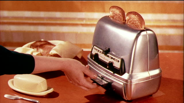 1958 MONTAGE HA MS Toast popping up out of toaster, woman's placing toast in warming tray beneath toaster / USA / AUDIO