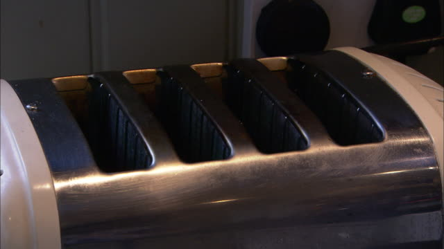 a toaster features four bread slots. - toaster appliance stock videos & royalty-free footage